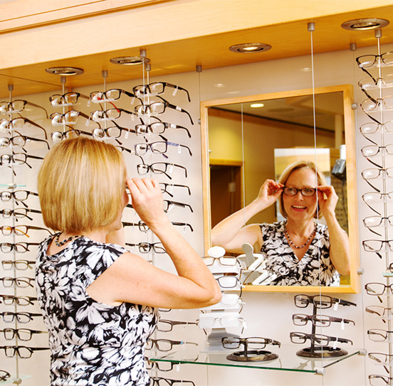 woman trying on eyeglasses in front of a wall of fashion eyeglass frames