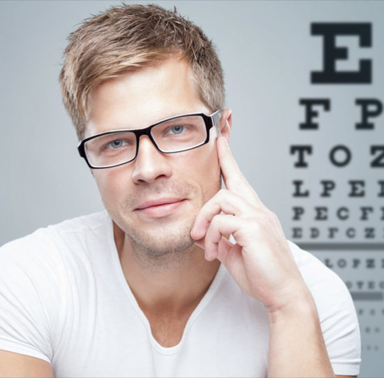 man with eyeglasses in front of eye test chart