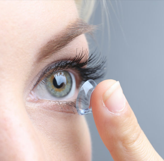 Proper eye care - woman putting in contact lens
